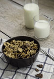 Golden and chocolate cornflakes in a bowl and a glass of milk on the wooden table. Golden and chocolate cornflakes in a bowl and a glass of milk on a wooden Stock Photography