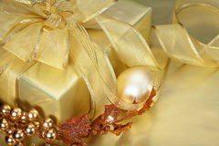 Golden Christmas. Beautiful Christmas Gift Wrapped in Gold with Decorations. Shallow DoF stock images