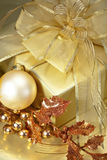 Golden Christmas. A Beautifully wrapped Christmas gift in gold with Decorations. Shallow DoF royalty free stock image