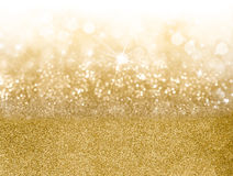 Golden Christmas background. With graduated bands of different sparkling and twinkling bokeh from party lights and glitter, full frame copyspace for your Royalty Free Stock Photo