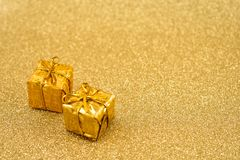 Golden Christmas background stock images. Golden holiday background with presents. Christmas gift boxes. Golden decorations on shiny background with copy space Royalty Free Stock Photos