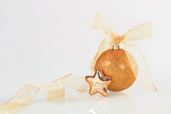 Golden christmas ball. Golden christmas ball and star with ribbon on white background Royalty Free Stock Photography