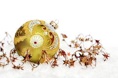 Golden christmas ball. On the snow over white background Royalty Free Stock Photos