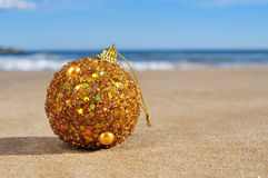 Golden christmas ball on the beach Royalty Free Stock Photo