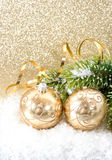 Golden christmas ball with christmas tree branch Royalty Free Stock Image