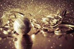 Golden Christmas ball and decorative metallic foil ribbon. Golden Christmas ball and decorative foil ribbon on a reflective surface against a blurred golden stock photo