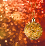 Golden christmas ball on the defocused background Royalty Free Stock Photos