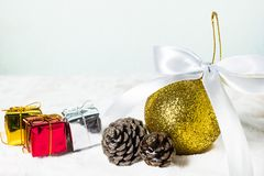 Golden Christmas ball and dry pine cones and gift box. On snow background with copy space. Christmas background concept Stock Image