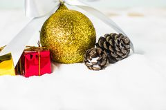 Golden Christmas ball and dry pine cones and gift box. On snow background with copy space. Christmas background concept Royalty Free Stock Photography