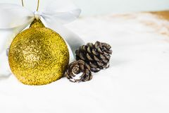 Golden Christmas ball and dry pine cones on snow background. With copy space. Christmas background concept Royalty Free Stock Photos