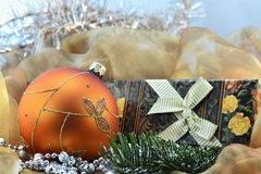 Golden Christmas ball and gift - closeup royalty free stock image