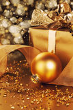 Golden christmas ball near christmas present Royalty Free Stock Images