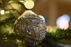 Golden Christmas ball with pictures of crystals. On the branches of a New Year tree on the background of yellow bokeh and highlights royalty free stock image