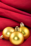 Golden christmas ball on a red silk cloth Stock Photos