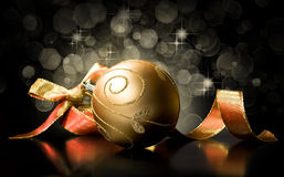Golden Christmas ball and ribbon on a black Royalty Free Stock Photography