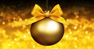 Golden christmas ball with ribbon bow on golden blurred lights b Royalty Free Stock Image