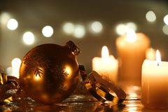 Golden Christmas ball with serpentine ribbon. Christmas ball with a golden serpentine ribbon and burning candles Stock Photography