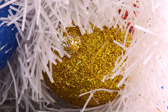 Golden christmas ball on shining glitter background close-up Stock Photo