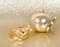 Golden christmas ball with streamer. Over golden shiny background Stock Photo
