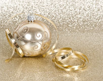 Golden christmas ball with streamer. Over golden shiny background Royalty Free Stock Photography