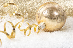 Golden christmas ball with streamer. Over golden shiny background in snow Stock Photo