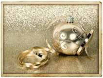 Golden christmas ball with streamer. vintage card. Golden christmas ball with streamer over golden shiny background. vintage post card design Stock Photos