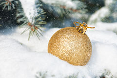 Golden christmas ball toy in snowfall Stock Photo