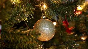 Golden Christmas ball on the tree with blinking lights background stock video