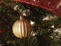 Golden Christmas ball tree decoration. Golden Christmas ball decoration hanging from the Christmas tree with a red ribbon Royalty Free Stock Photo