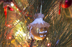 Golden Christmas ball, which has a mill shape, on Christmas tree Stock Photos