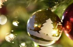 Golden Christmas ball with white pictures. On a branch of a green holiday spruce with yellow bokeh and highlights stock images