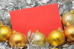 Golden christmas balls and card. In silver garland background Stock Photos