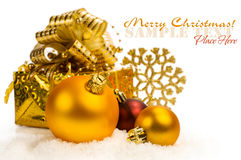Golden Christmas balls and gift box in the snow Stock Photography