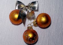 Golden Christmas balls and gold bow. Three gold Christmas ball and gold bow on a light background Royalty Free Stock Photo