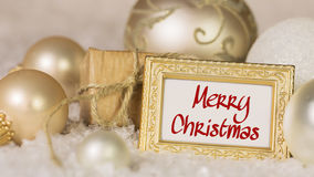 Golden christmas balls and greeting text Merry Christmas. Royalty Free Stock Photos