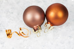 Golden Christmas balls on icy background Stock Photos