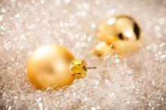 Golden christmas balls lying in silver tinsel Stock Photo