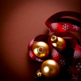 Golden christmas balls with red gift ribbon stock photography