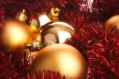 Golden Christmas balls on red tinsel Stock Photos
