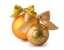 Golden Christmas balls with silk ribbon bows. On white background Royalty Free Stock Image
