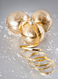 Golden christmas balls with snow decoration. Golden shiny christmas balls with snow decoration over silver background stock photos
