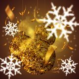 Golden christmas balls with sparkles, with confetti and snowflakes. On a yellow gradient background Royalty Free Stock Image