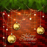 Golden Christmas balls and spruce branches on a brick wall Royalty Free Stock Photos