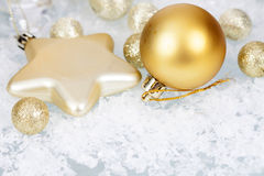 Golden Christmas balls and star on icy background Stock Photography