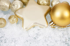 Golden Christmas balls and star on icy background Royalty Free Stock Photos
