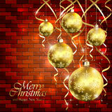 Golden Christmas balls and tinsel on a brick wall Stock Images