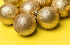 Golden Christmas balls toys lie on background. Golden Christmas balls toys lie on a yellow background royalty free stock images
