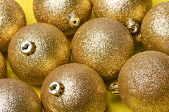 Golden Christmas balls toys lie on a yellow. Background royalty free stock photo