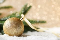 Golden christmas bauble. With ribbon and fir-tree branches on lights background Stock Photography