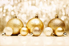 Golden Christmas baubles. An arrangement of golden Christmas baubles against a festive bokeh of twinkling gold lights with copyspace Stock Image